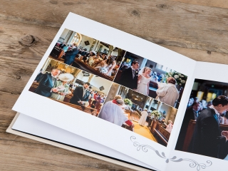 wedding album on a wooden floor opened to two pages