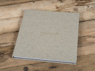wedding album closed on a wooden floor with a fabric cover reading husband and wife