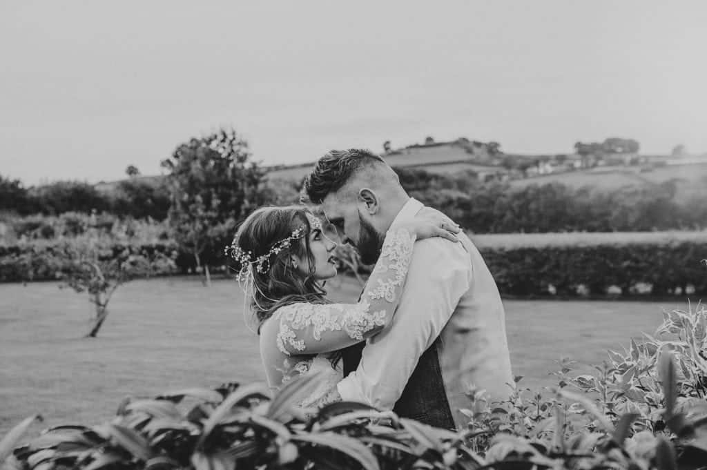 Cardiff wedding photographer - Bride & Groom stood behind a bush about to kiss with forehead's touching