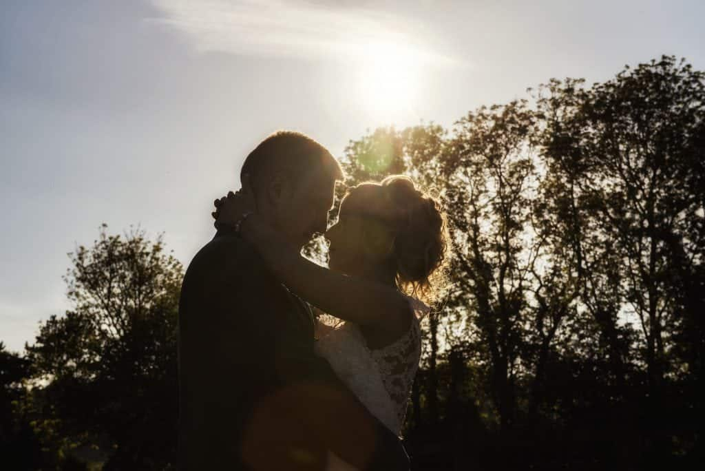 Bride & Groom embrace in sunlight wedding photographers cardiff