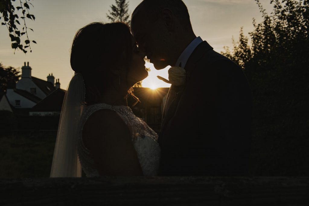 South Wales Wedding Photographer ~ Couple kissing at sunset