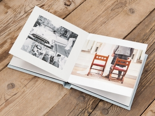 a wedding album open on a wooden floor showing the pages