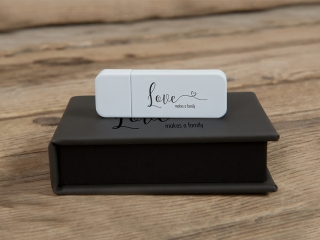 Small black leather case with a white usb stick on a wooden floor