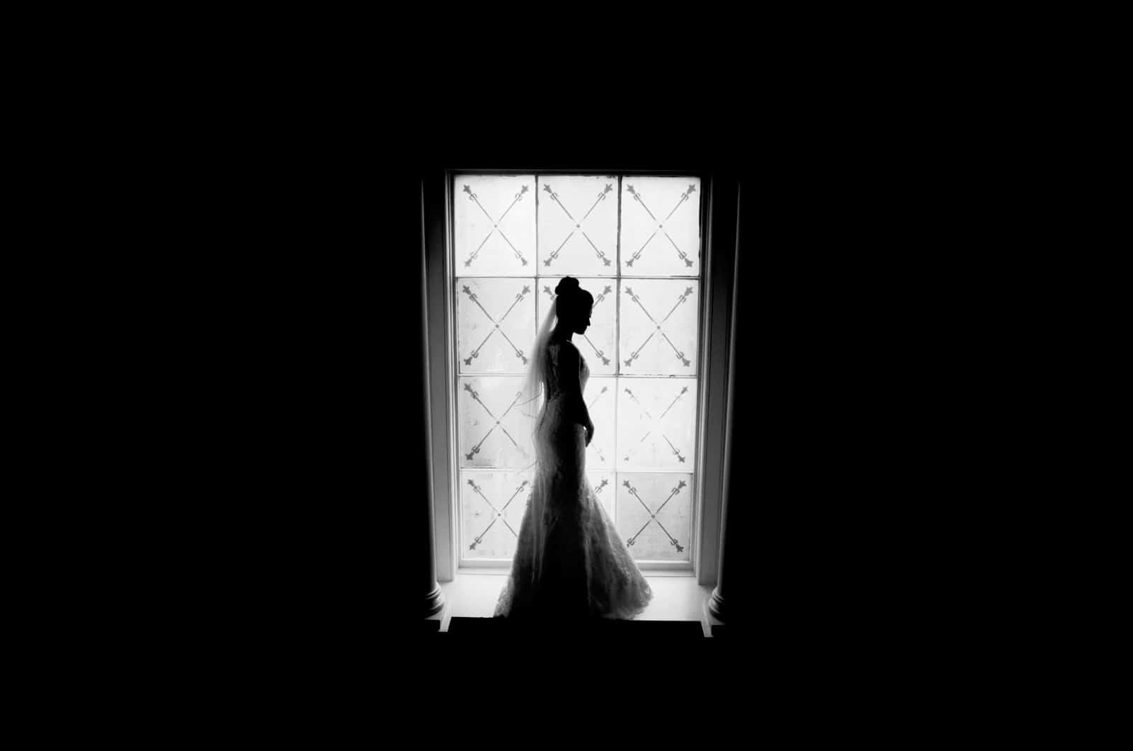 Bride stood in window wedding photographers cardiff