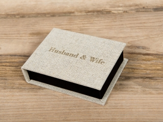 Small hessian case with  husband and wife written on it on a wooden floor