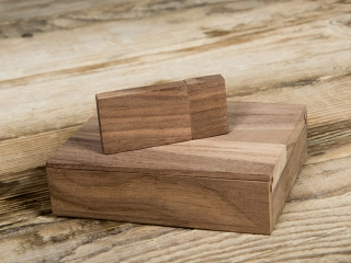 Small wooden case with a wooden usb stick on a wooden floor