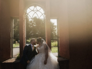 Bride & Groom kiss in window wedding photographers cardiff