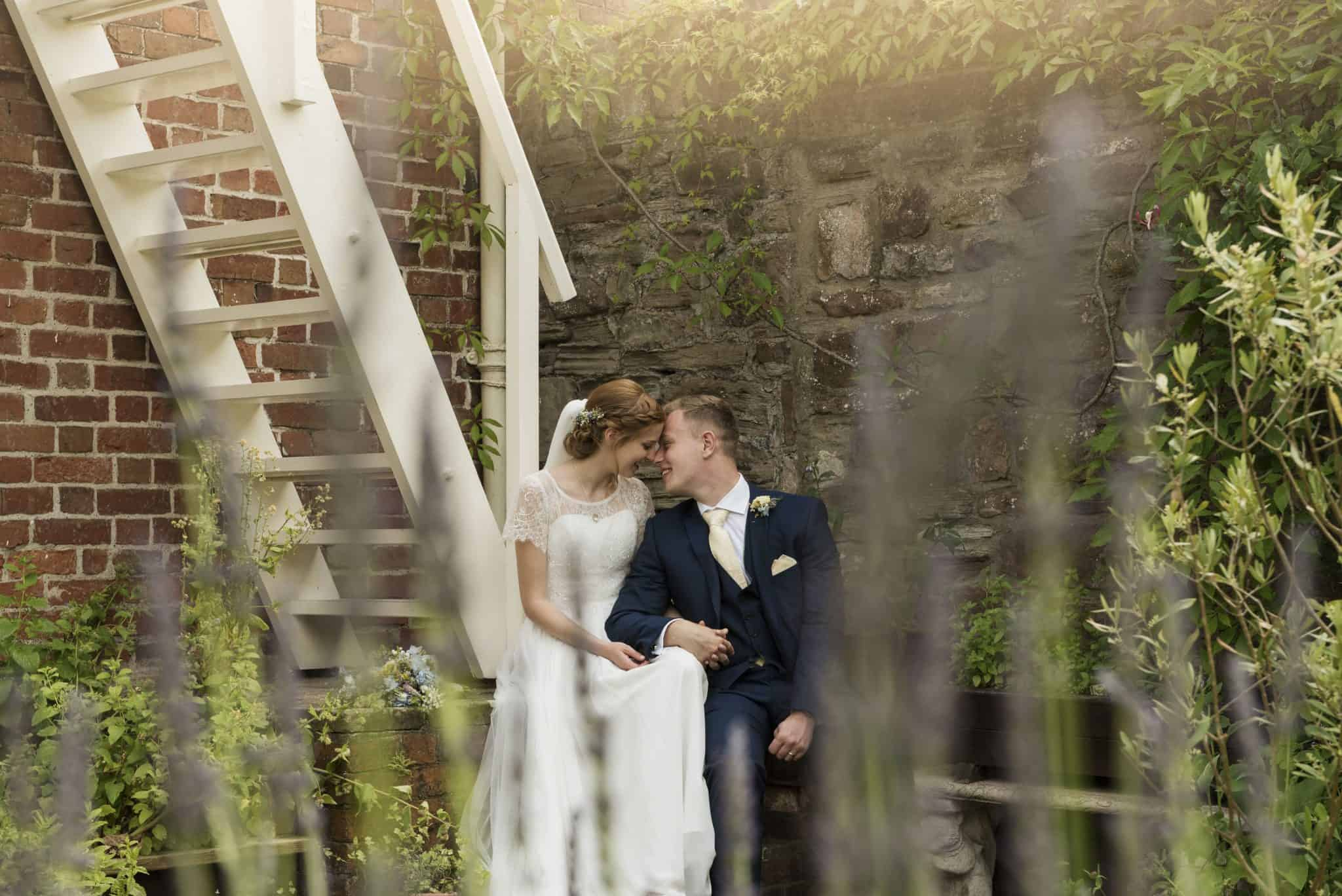 Bride and groom kiss on stairwell wedding photographers cardiff