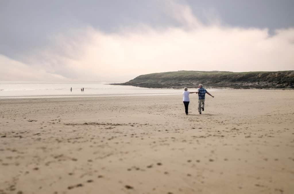 Couple skipping across the beach