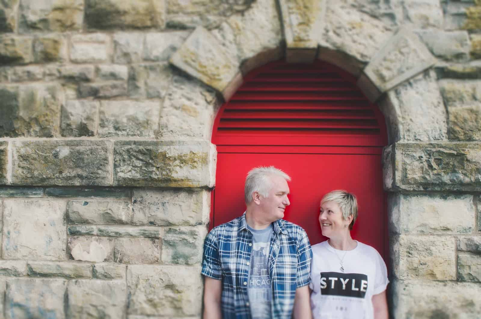Couple stood in doorway with a red door