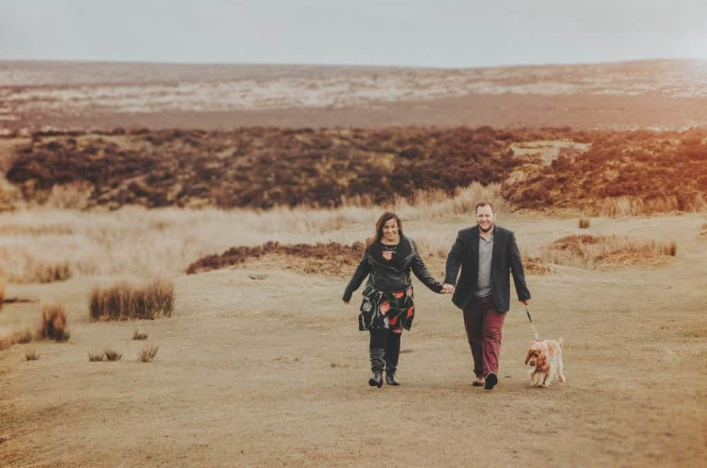 Couple walking their dog over a moor