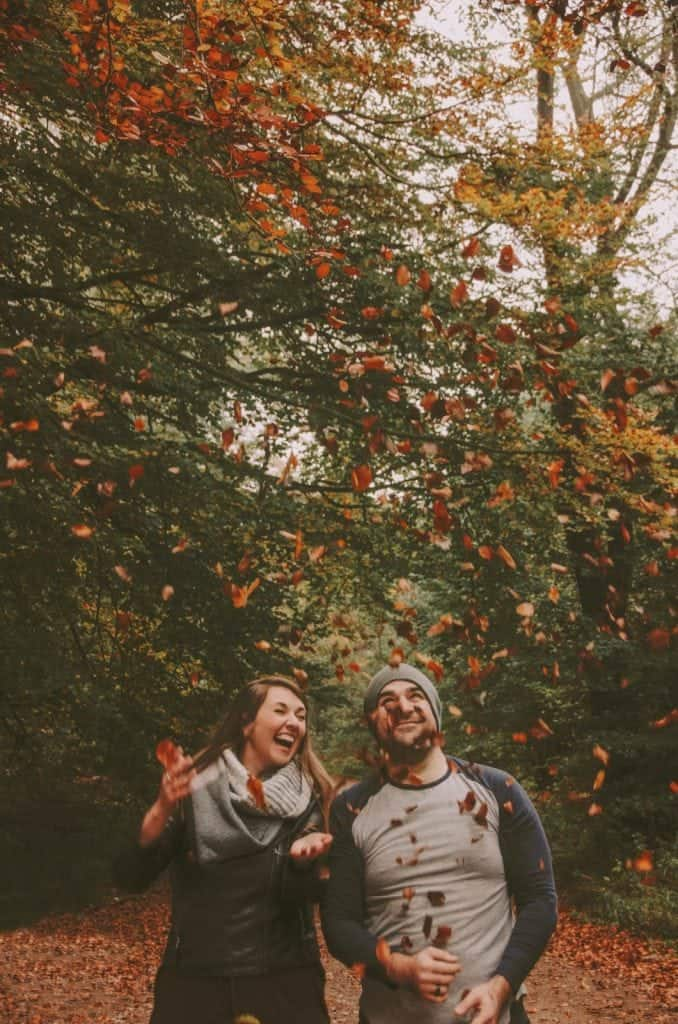 Couple laugh as they throw dried leaves in the air