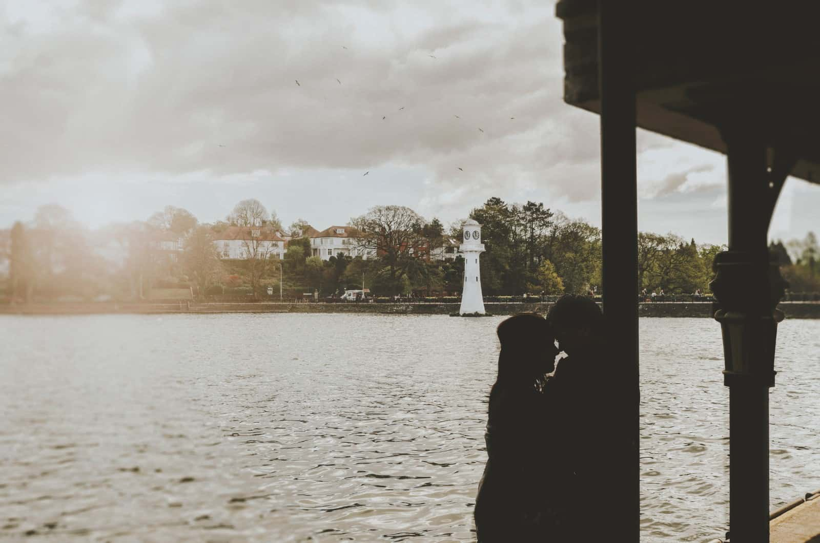 Couple Silhouetted against Roath park Lake Cardiff