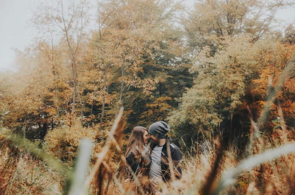 Couple look at each other in tall grass