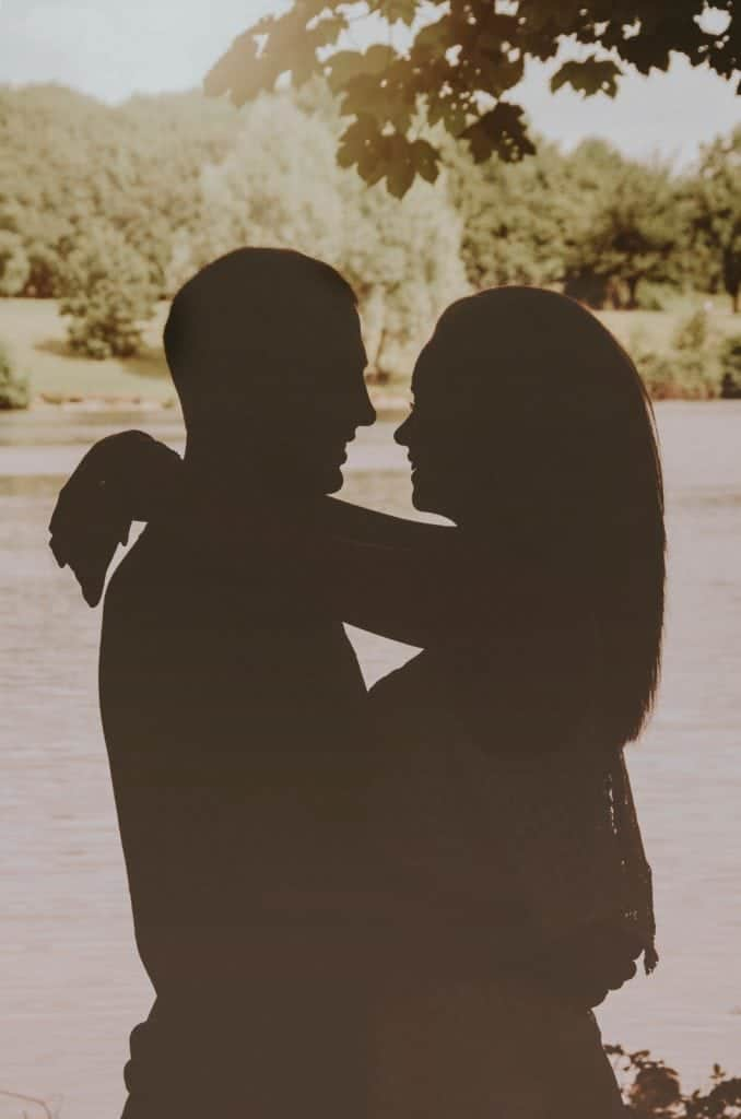 Couple silhouetted against a lake