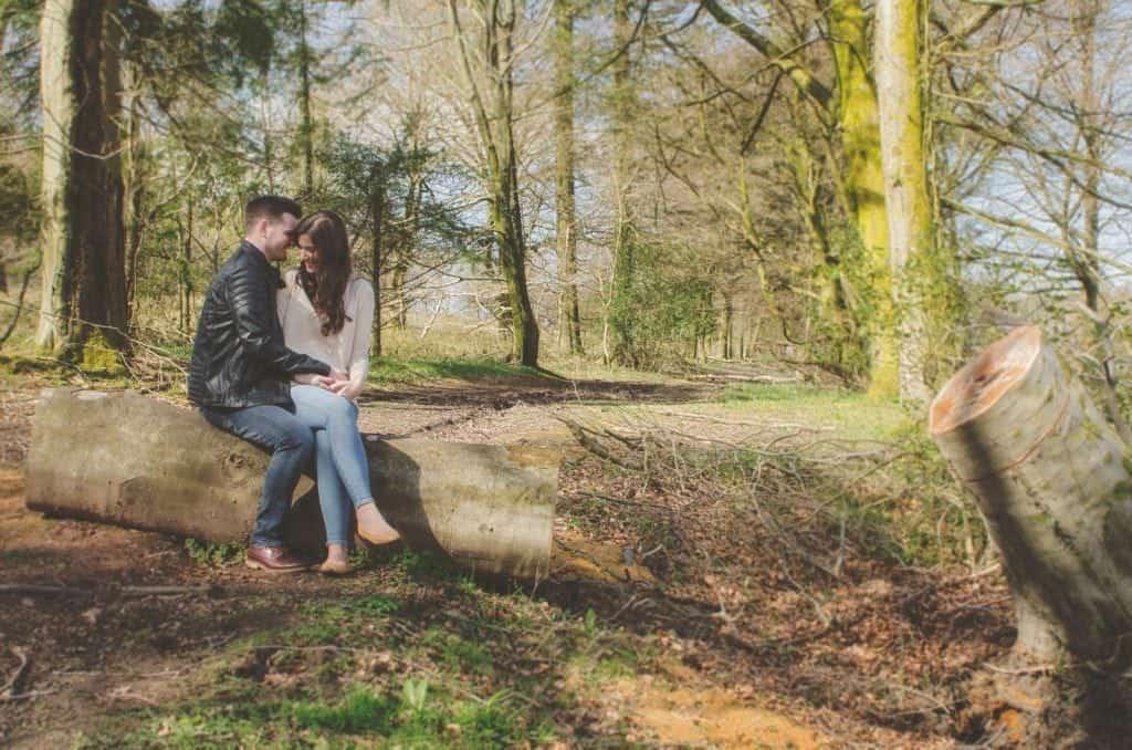 Couple sat on fallen tree smiling