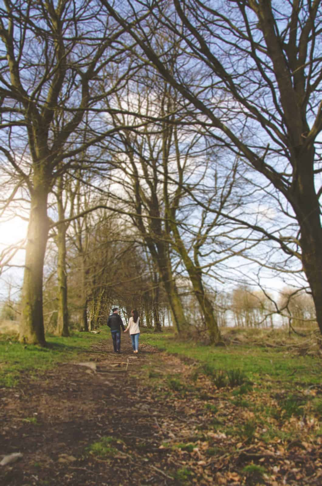 Couple walk hand in hand down tree lined path