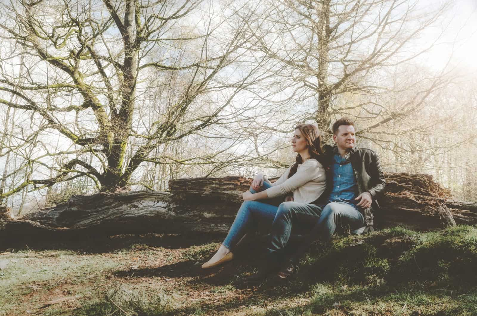 Couple sat on hill against a fallen tree