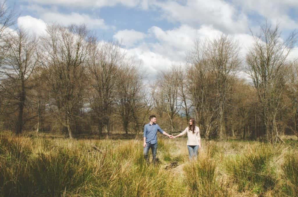 Couple looking at each other standing in long grass holding hands