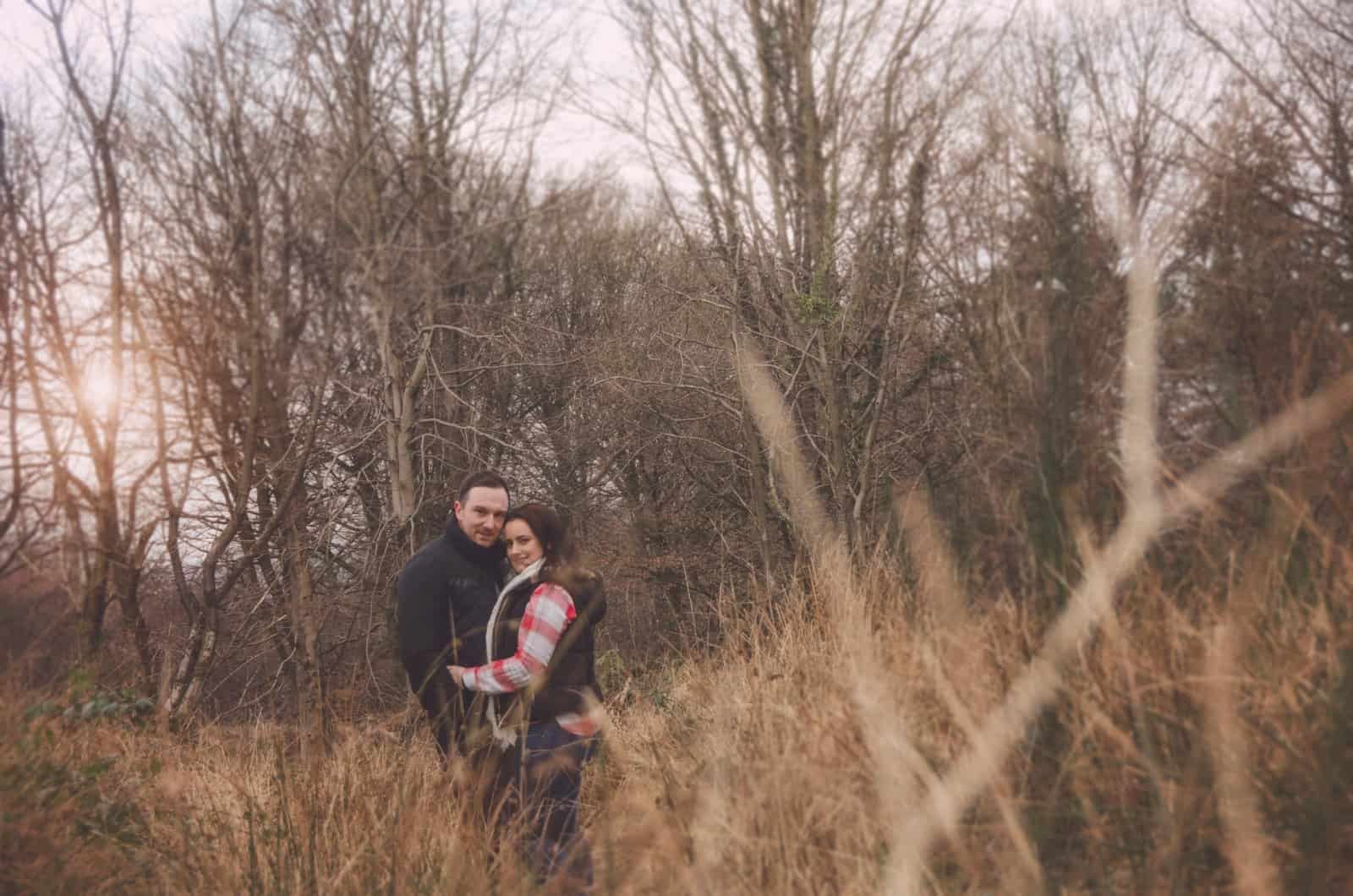 Couple stood together in long grass