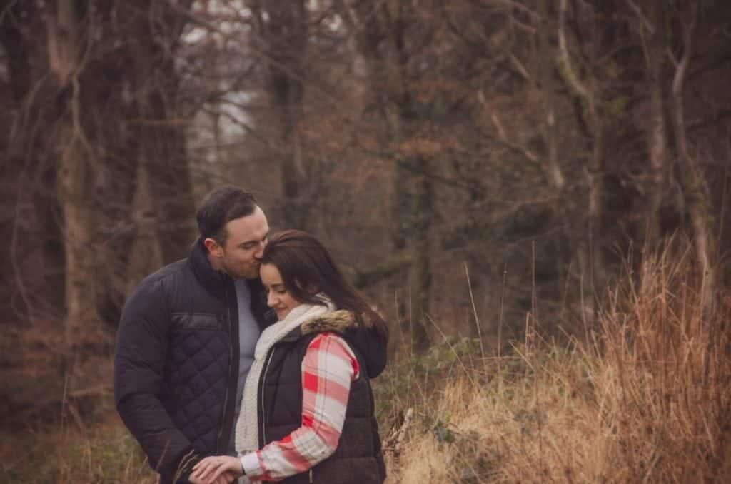 Man kissing woman's head