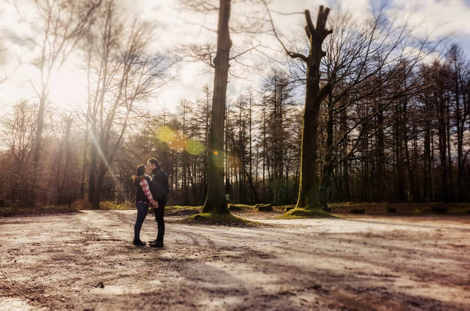 Couple stood in frosty forest with sun rays cutting through trees