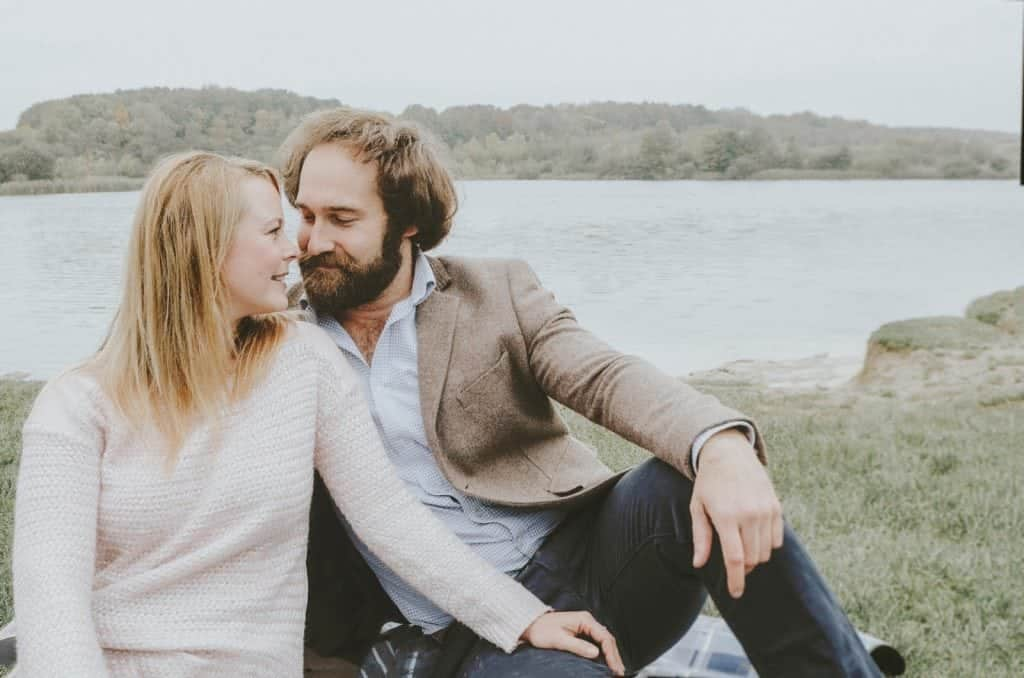 Couple sat in front of lake looking at each other