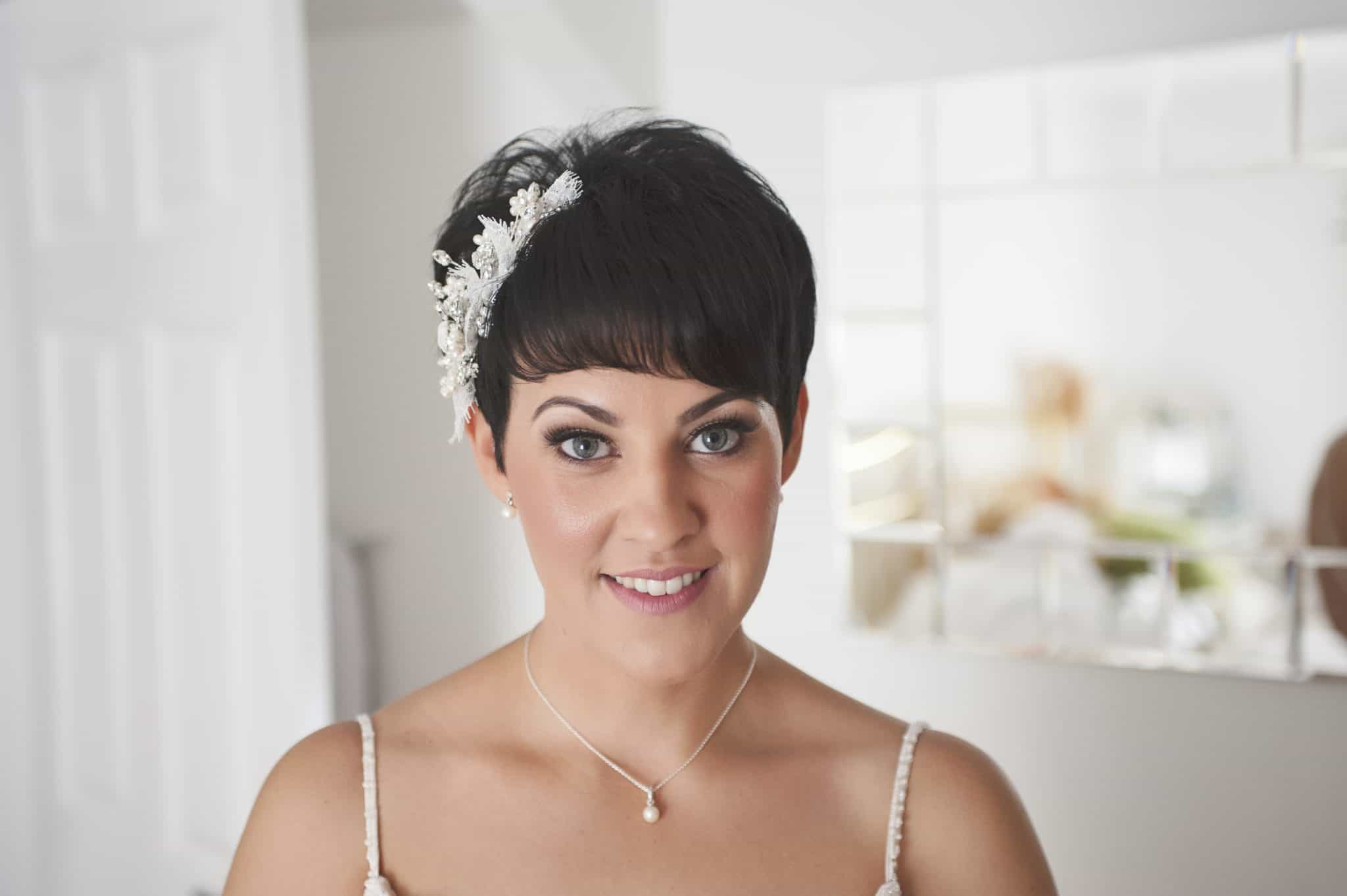 Bride in bedroom looking straight at camera smiling