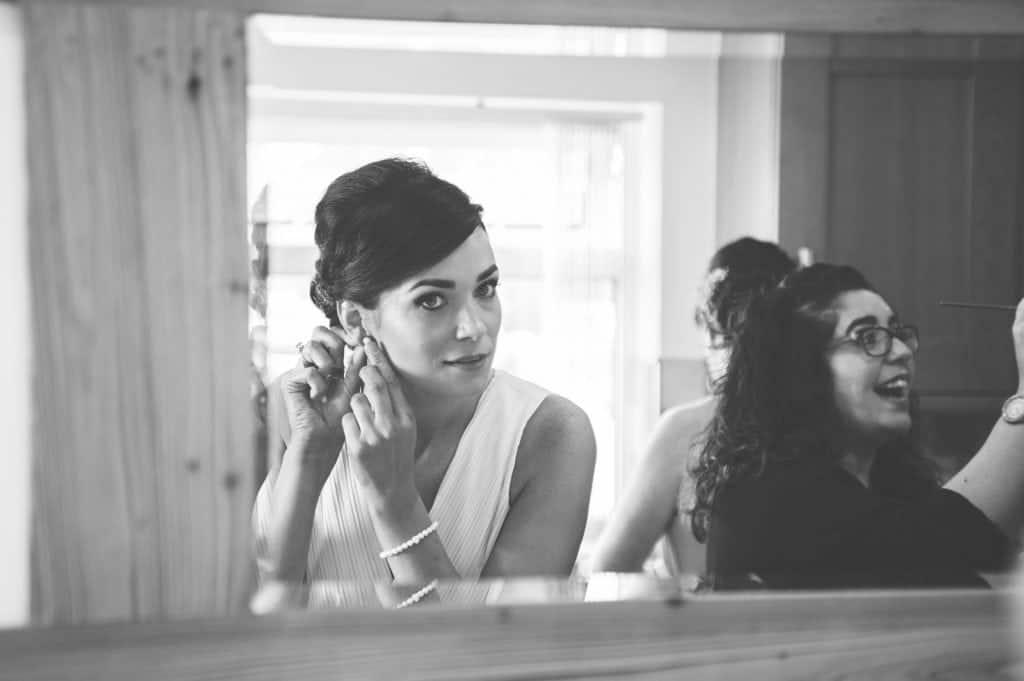 Bridesmaid putting her earrings in in mirror