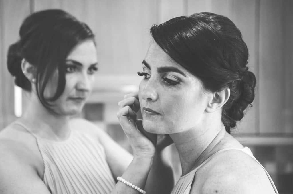 Bridesmaid putting on jewellery