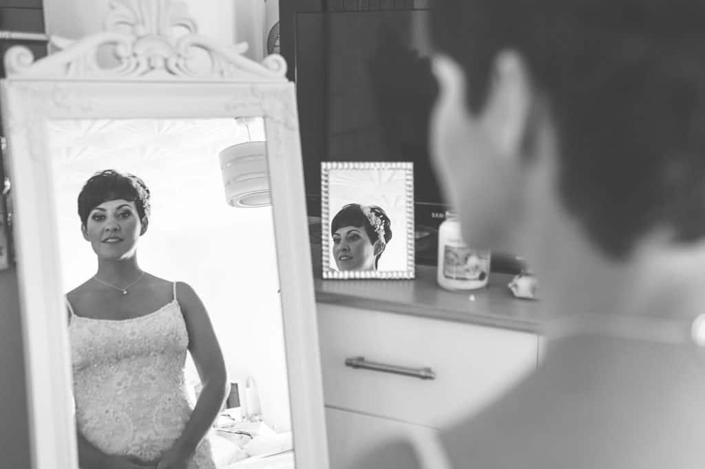 Bride stood in bedroom looking in mirror
