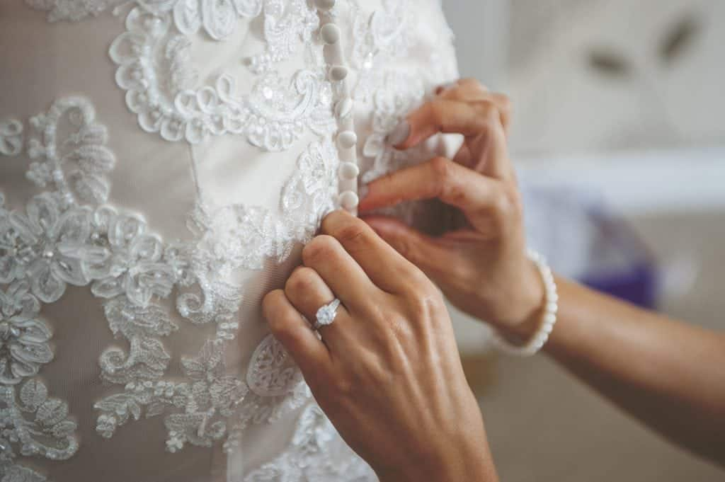 Back of the bride's dress being buttoned