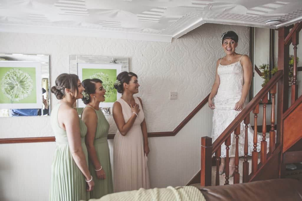 Bride coming down stairs for first time in her wedding dress