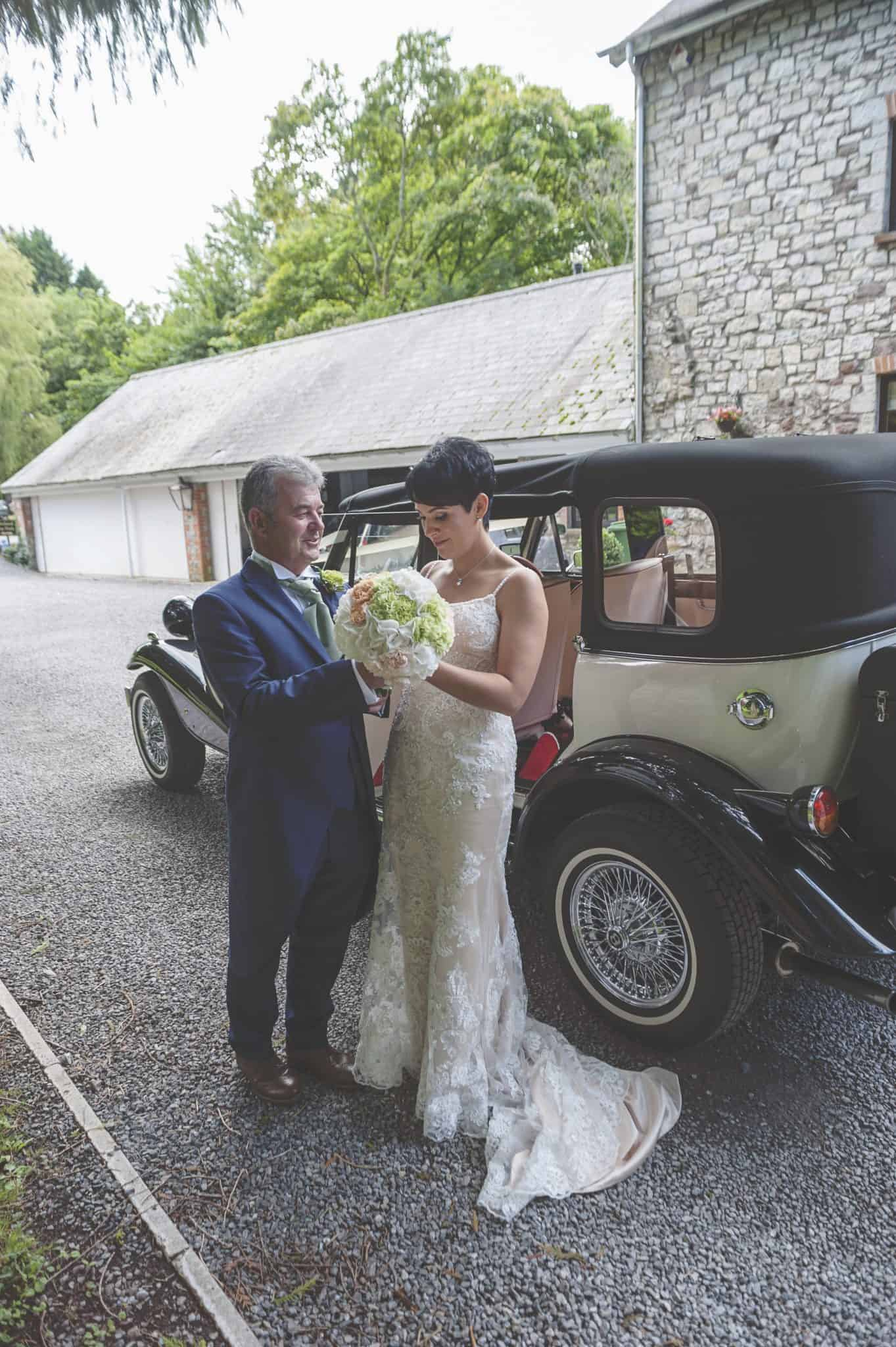 Bride and her father stood outside wedding car