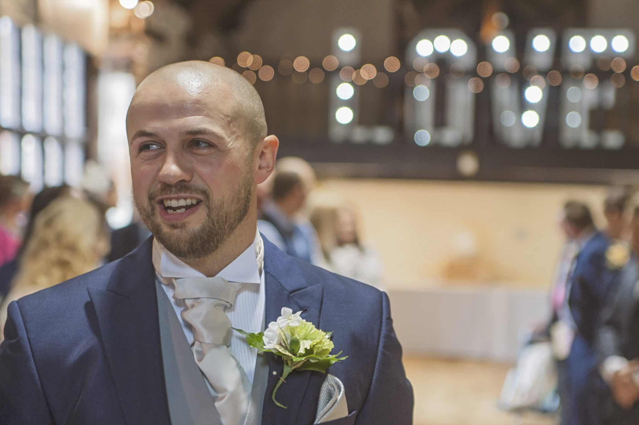 Groom stood at end of wedding aisle smiling