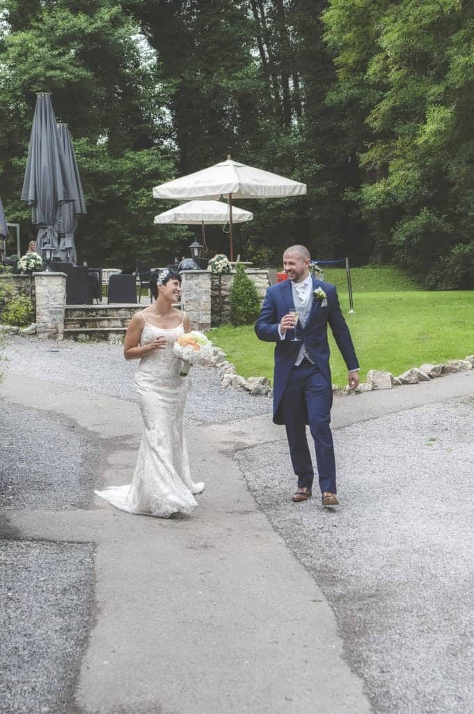 Bride and groom walking across the forecourt of pencoed house estate