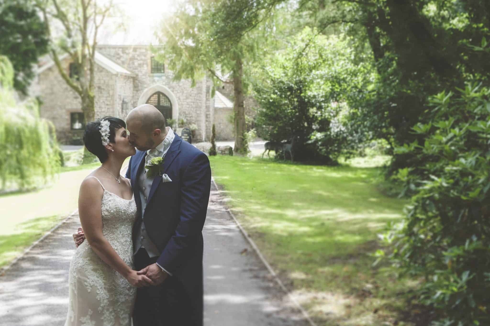 Bride & Groom stood looking at each other on the pathway of Pencoed House Estate kissing