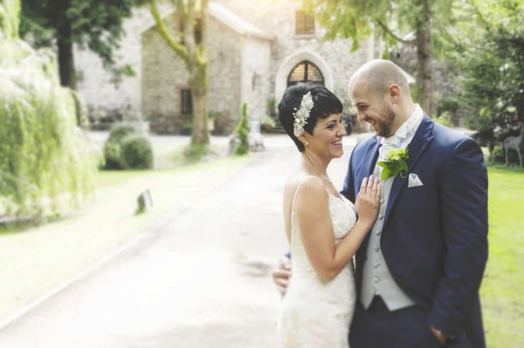 Bride & Groom stood on the pathway of Pencoed House Estate laughing