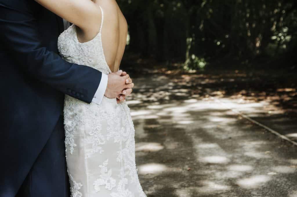 close up of groom's arms around bride's waist