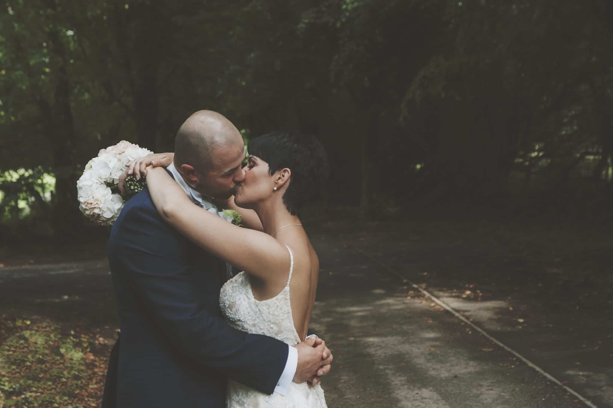 bride and groom kissing on tree covered pathway
