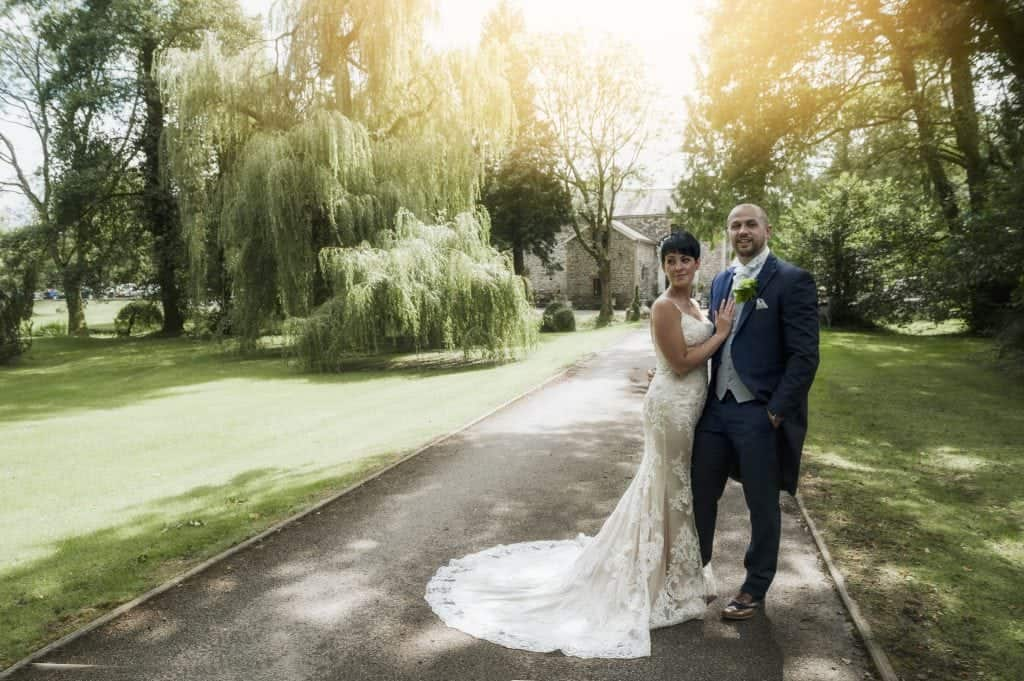 Bride & groom stood on pathway with wedding venue in background