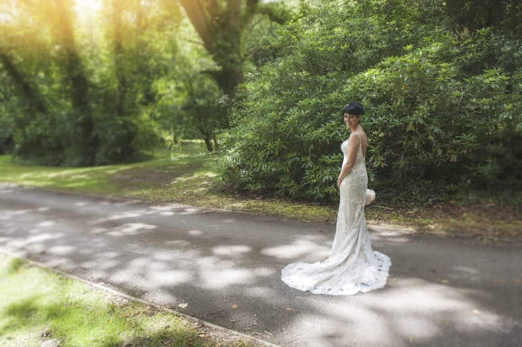 Bride stood side on looking over should on hedged pathway at Pencoed House Estate smiling