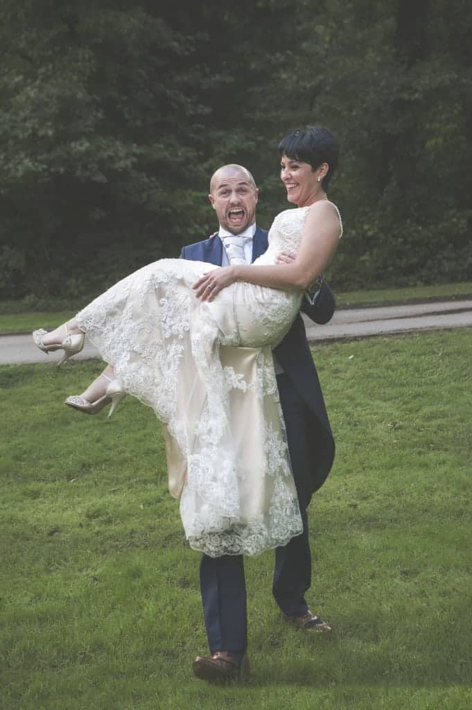 Groom carrying bride over grass