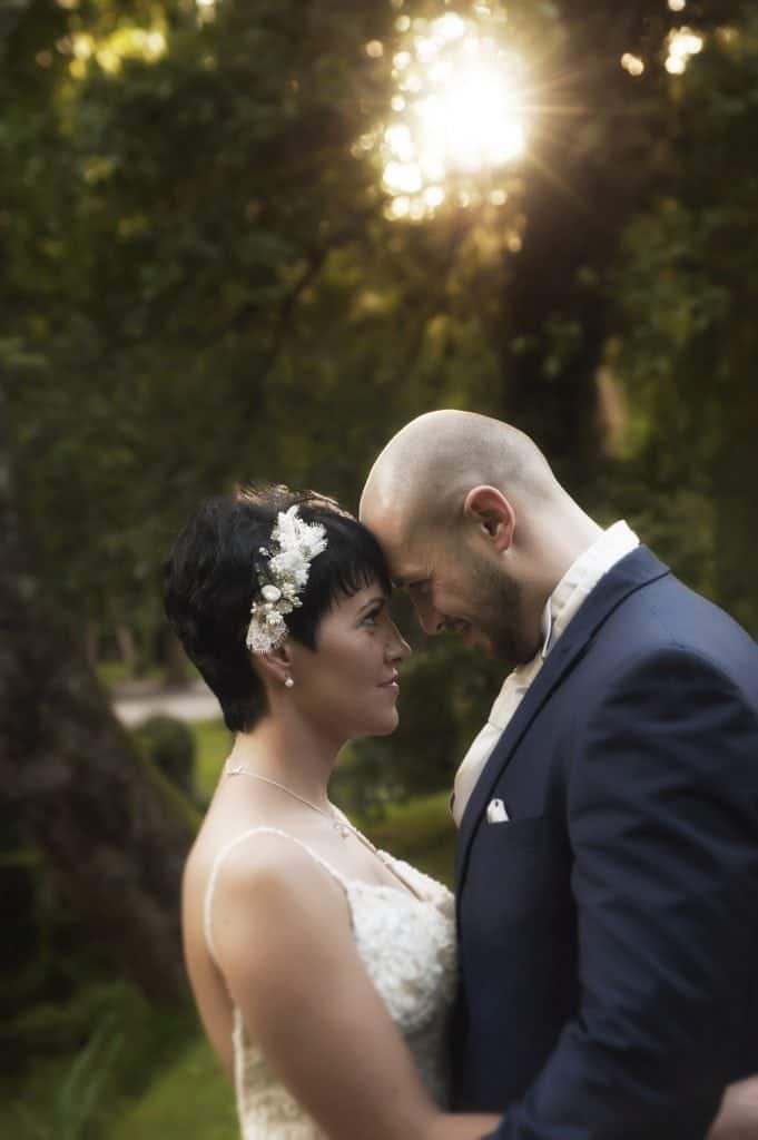 Bride and groom stood forehead to forehead din sunshine