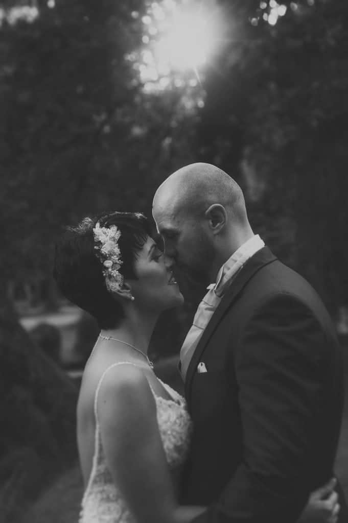 Black & white photo of bride and groom about to kiss
