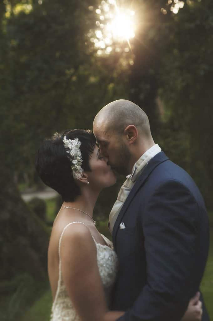 bride & groom kissing with sunbeam in background