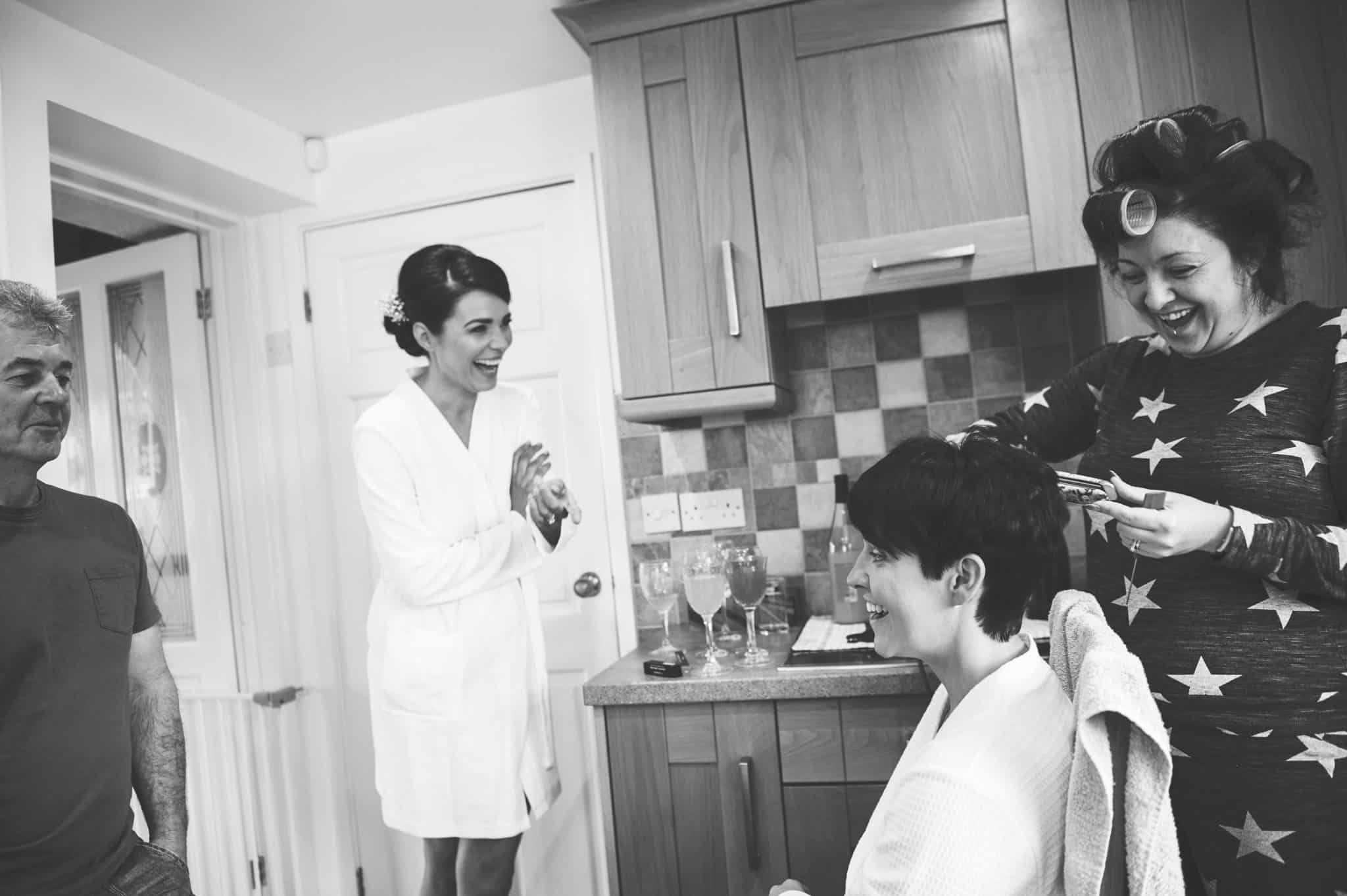 Bride and bridesmaid laughing in kitchen whilst bride has her hair done