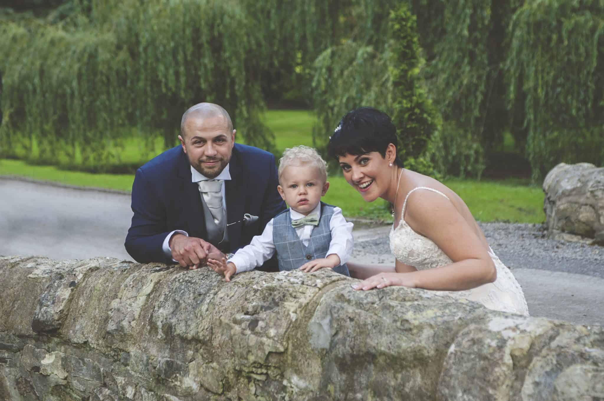 bride & groom sat on bridge with page boy