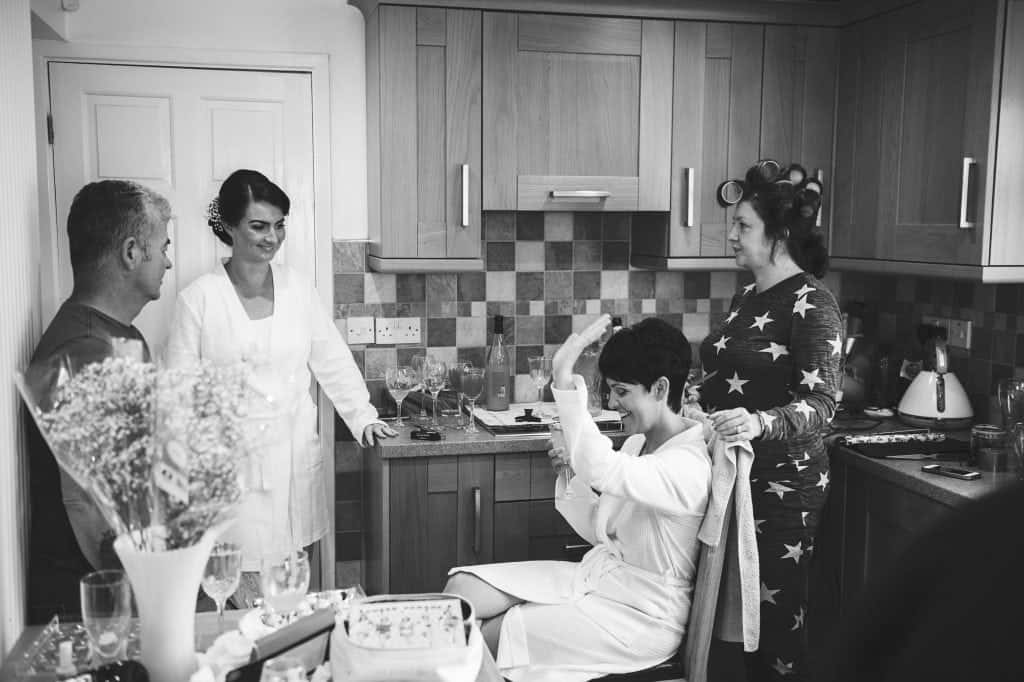 Bride sat in kitchen having  her hair done high fiving
