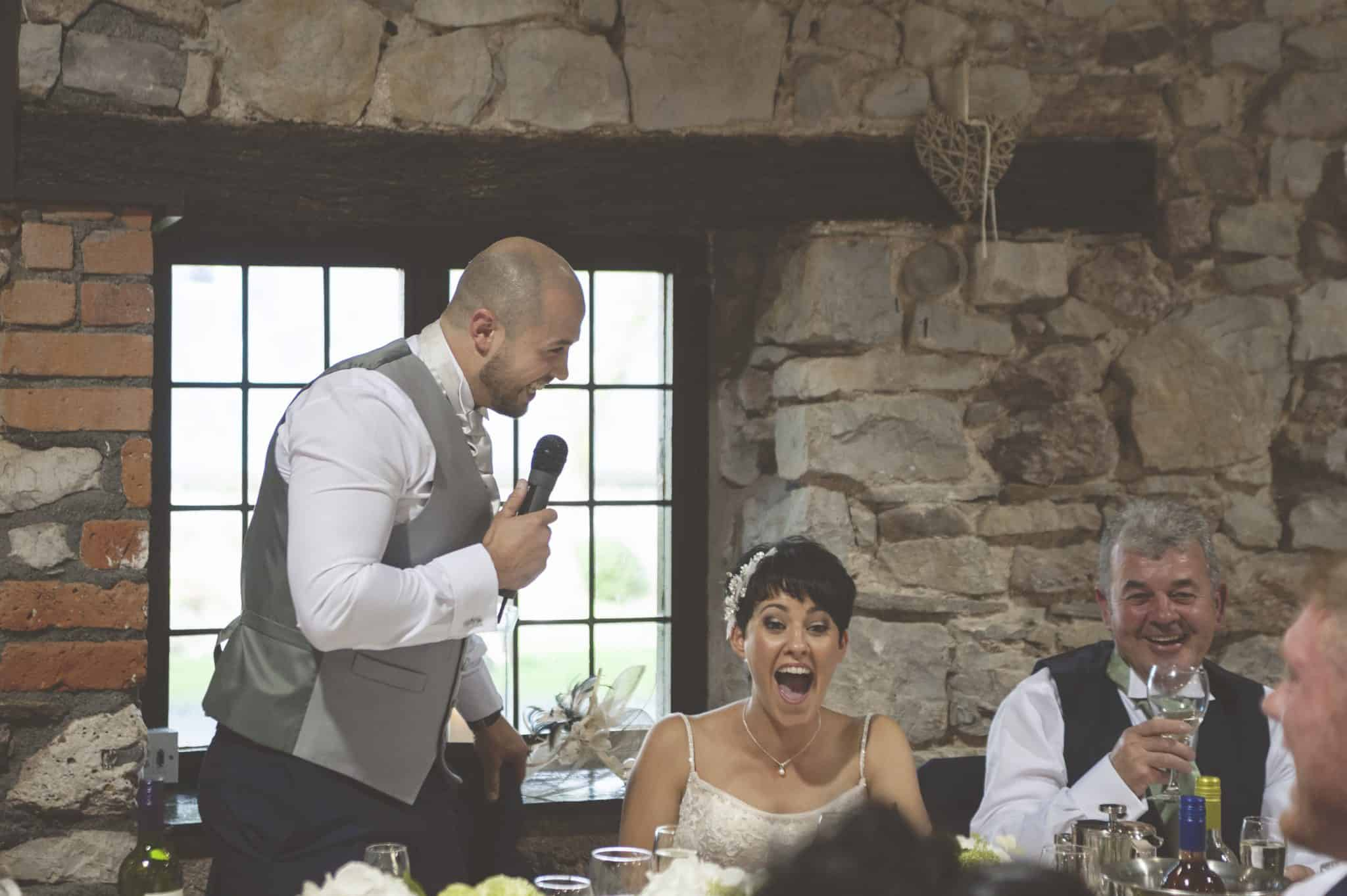 Groom giving his speech and bride laughing